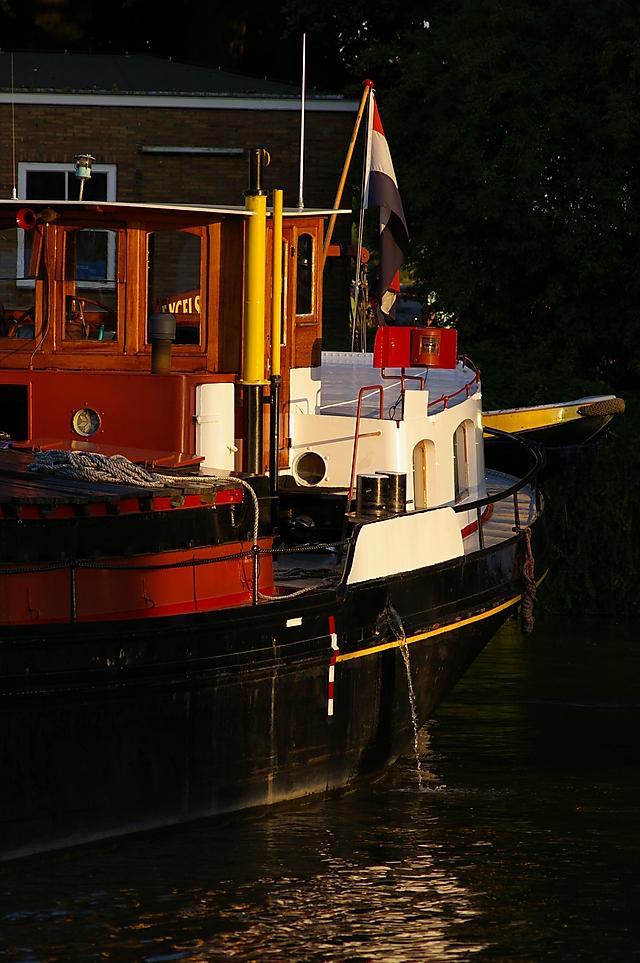 Motorschip excelsior tijdens de draai in het gouden avondlicht