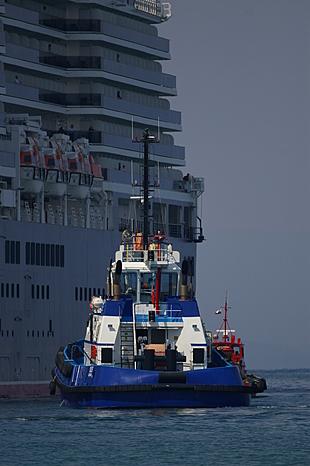 De sleepboot Ixus helpt met uitvaren