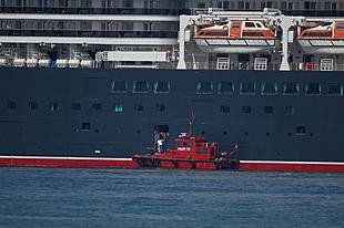 De loods stapt van QV af naar de loodsboot