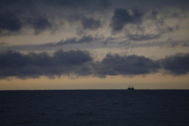 Een vissersboot rept zich naar huis