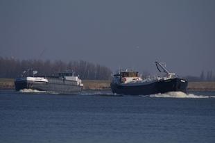 Snelle en langzame vrachtboot in de bocht van de Oude Maas