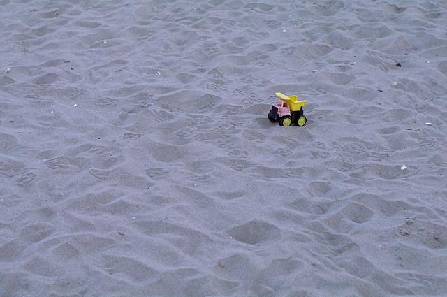 Arm vrachtwagentje, achtergelaten op het grote, lege strand...