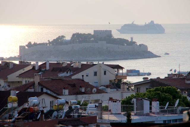 Blik vanaf ons dakterras bij laaghangende zon. Een cruiseschip kiest de route tussen Turkije en het Griekse eiland Samos.